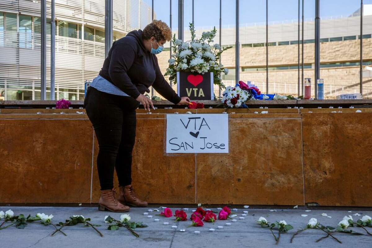 Kiana Simmons places flowers Wednesday at a vigil at San Jose City Hall for victims of the mass shootings.