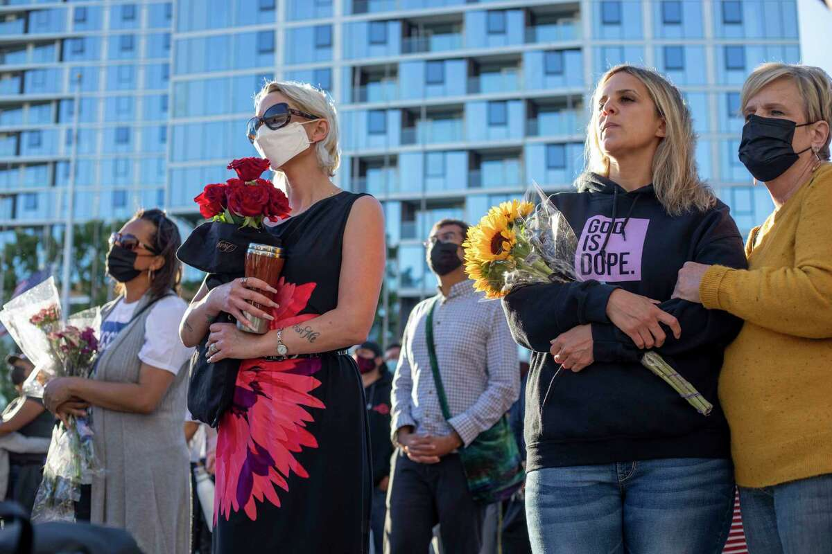 """Kristine Gardner, left, Alexandra Galvan and her mother, Tina Galvan, listen to speakers at a vigil in San Jose on Thursday, the day after a """"a highly disgruntled"""" Valley Transportation Authority employee killed himself and nine other workers at a light-rail facility."""