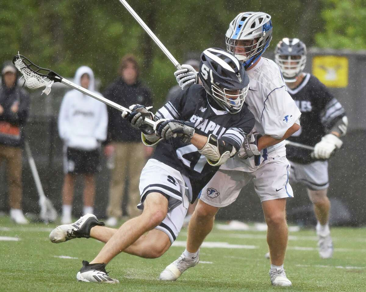 Staples' Charlie Howard (21) battles for a shot against Darien defenseman Sam Erickson (7) during the FCIAC boys lacrosse final at Dunning Field in New Canaan on May 28.