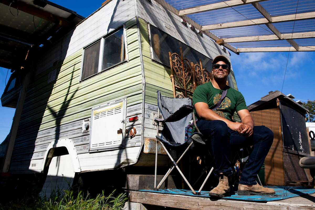 Neighborship co-operative village founder Adam Garrett-Clark sits on the porch of the communal trailer space where a handful of people are living in RVs in a communal setting on a lot in West Oakland. Oakland is proposing an ordinance that would make tiny homes with wheels and recreational vehicles legal dwellings.