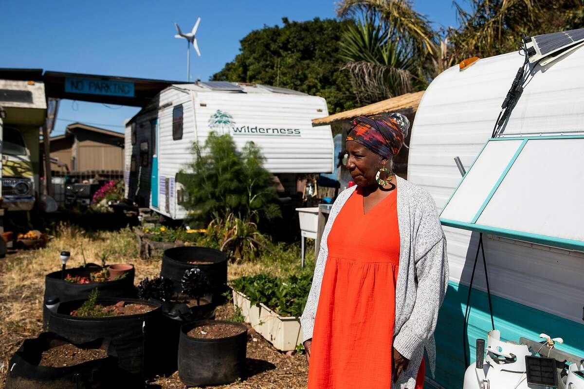 Sauda Garrett, the mother of Neighborship co-operative village founder Adam Garrett-Clark, stands outside of her RV in West Oakland.