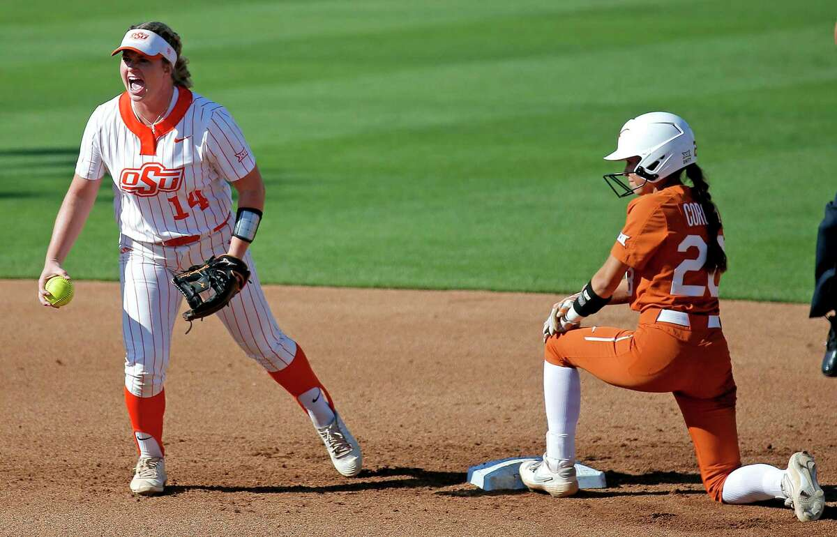Oklahoma State's Karli Petty (14) celebrates after tagging out Texas' Camille Corona (28) on an attempted steal in the fifth inning.
