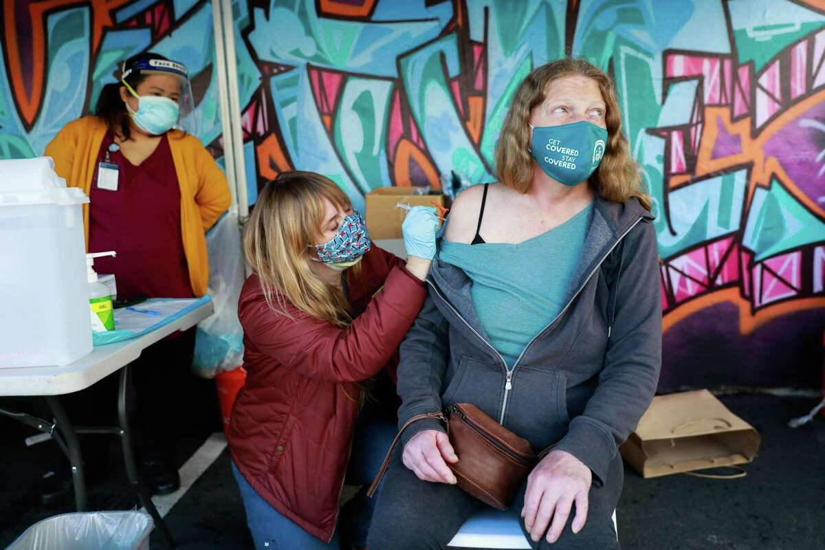 Nurse Tara O'Flaherty (left) administers the Johnson & Johnson COVID-19 vaccine to Victoria Warnke in Oakland at the Trust Clinic.