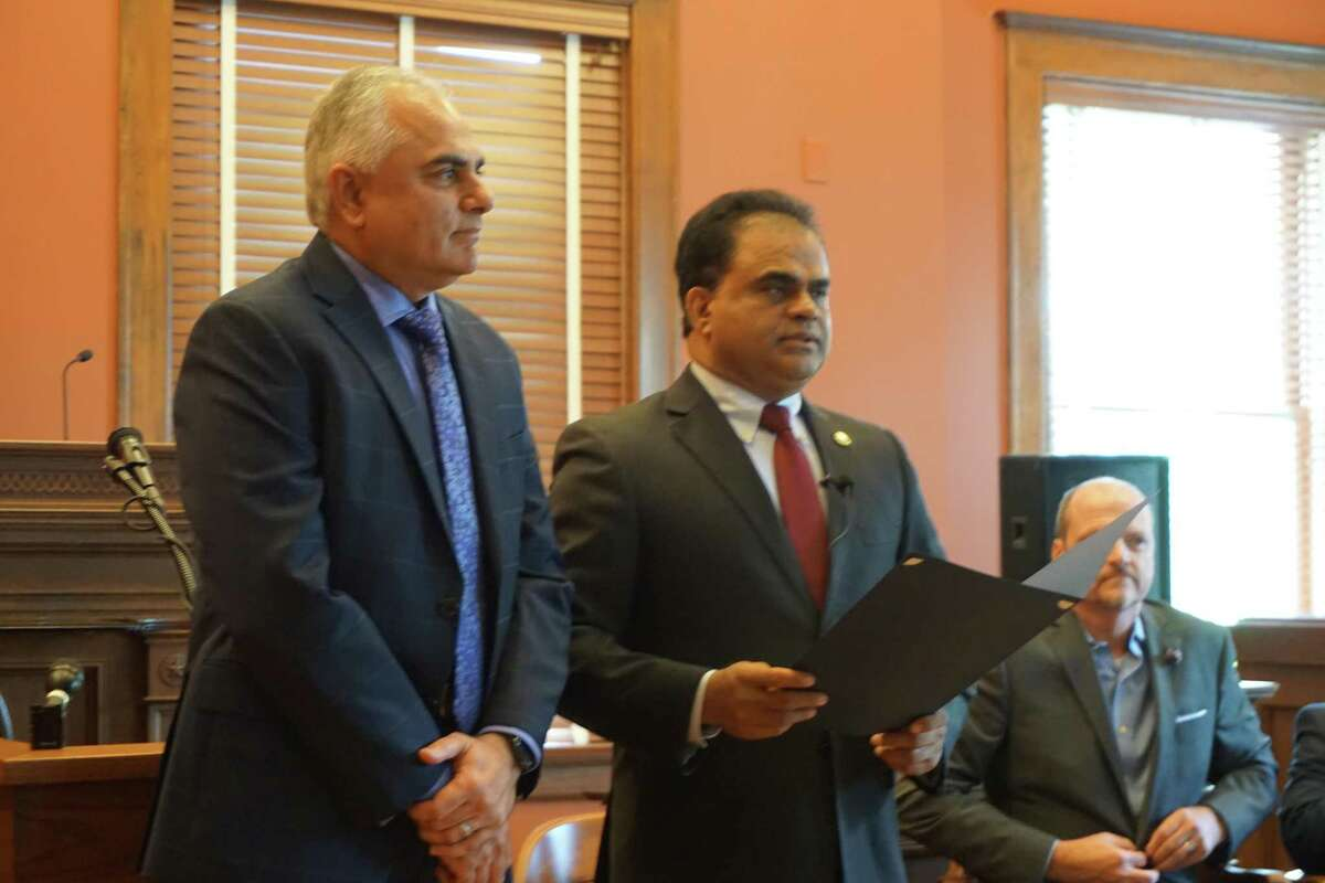 Fort Bend County Judge KP George, right, reads a proclamation recognizing the work in mental health of Dr. Asim Shah, executive vice-chair and professor of psychiatry and family and community medicine at Baylor College of Medicine, left, during a ceremony on Friday, May 28, at the Fort Bend County Historic Courthouse in Richmond.