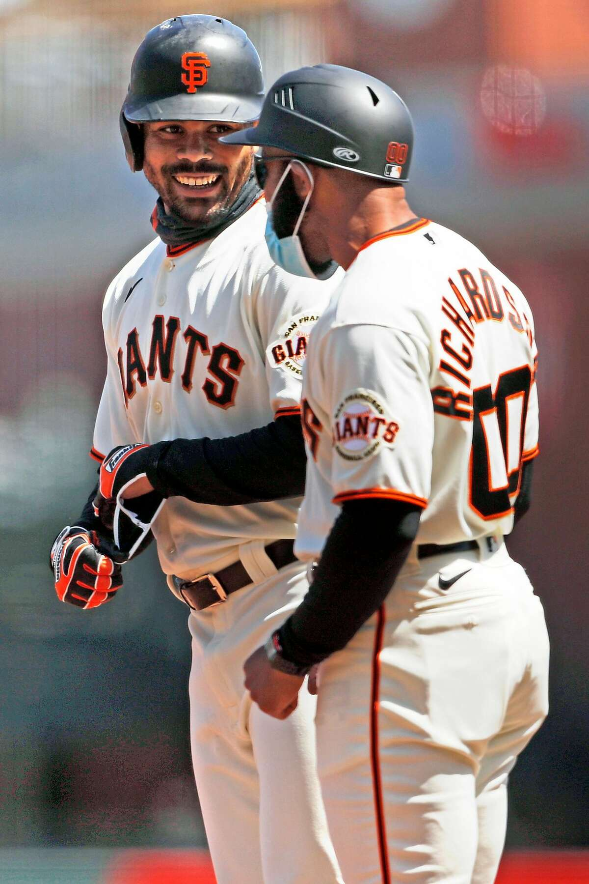 San Francisco Giants' LaMonte Wade, Jr. smiles at first base coach Antoan Richardson after Wade, Jr. singled against Colorado Rockies in 2nd inning during MLB game at Oracle Park in San Francisco, Calif., on Sunday, April 11, 2021.