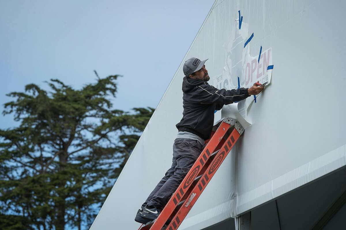 Chris Alvarez applies a tournament sign to a tent at the Lake Course, host to the U.S. Women's Open for the first time.