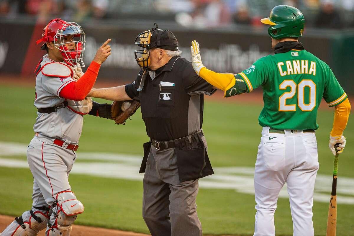 Umpire Larry Vanover gets between Angels catcher Kurt Suzuki and Mark Canha after a fastball buzzed the batter.