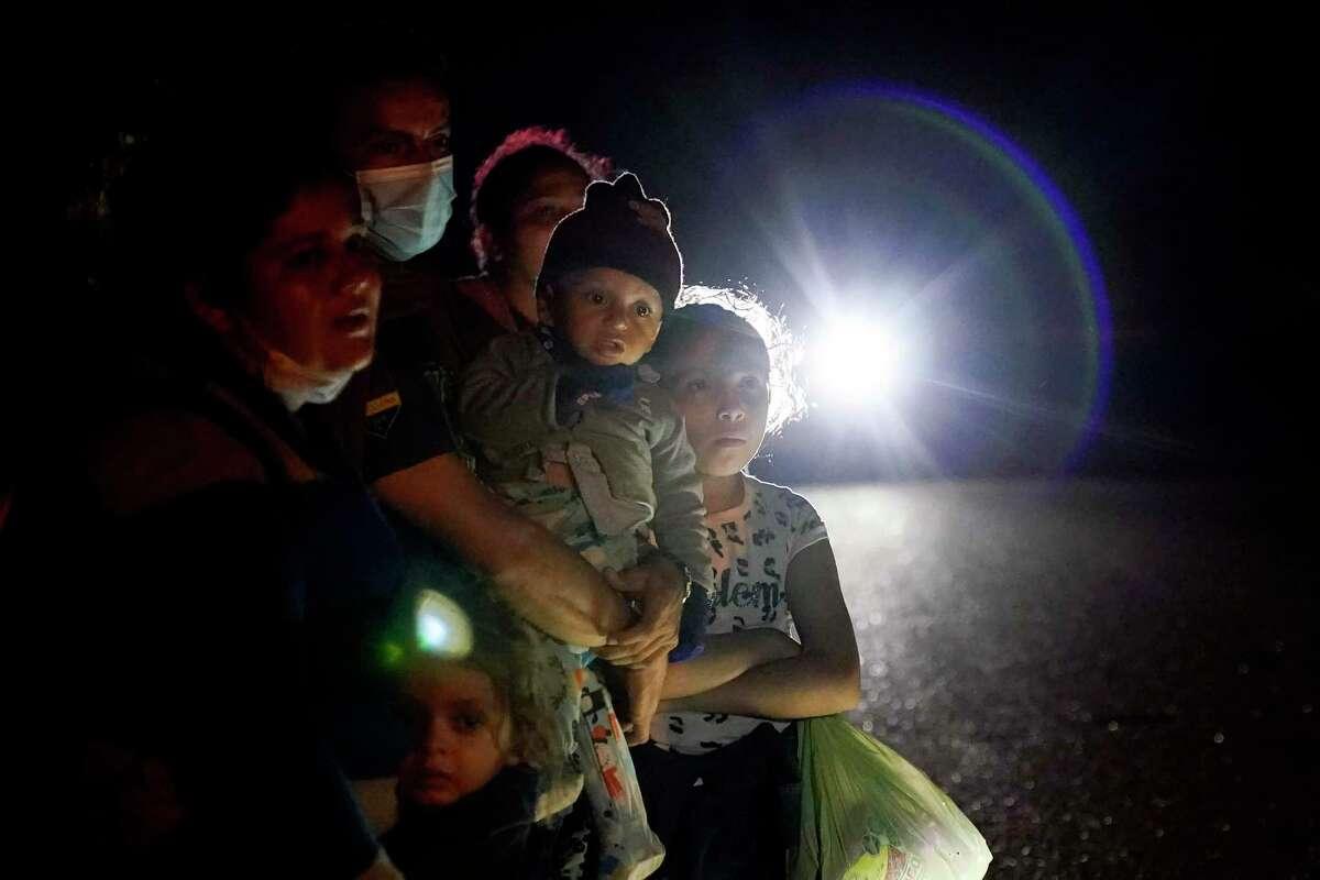 En esta fotografía del 17 de mayo de 2021 se muestra un grupo de migrantes procedentes de Honduras y Nicaragua que esperan en un camino luego de que se entregaron a las autoridades en La Joya, Texas.