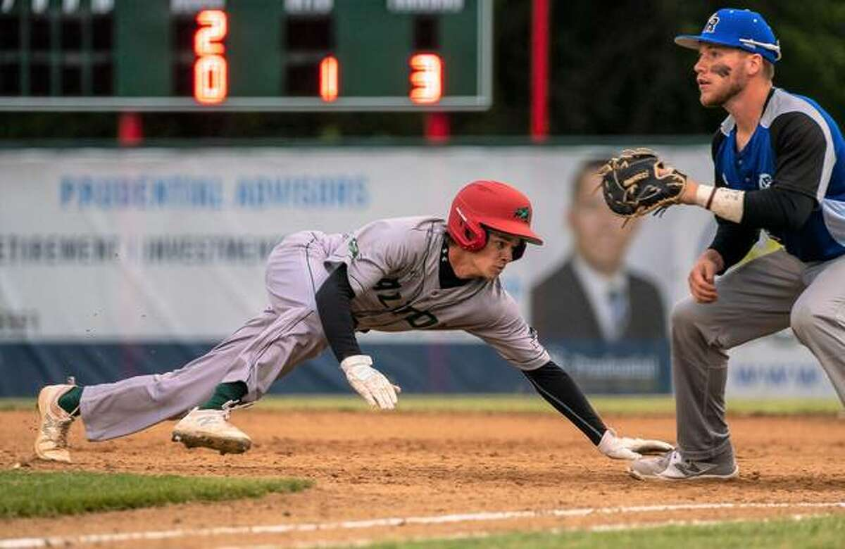 Alton River Dragons outfielder Blake Burris dives safely back into first base on a pickoff throw Friday night.