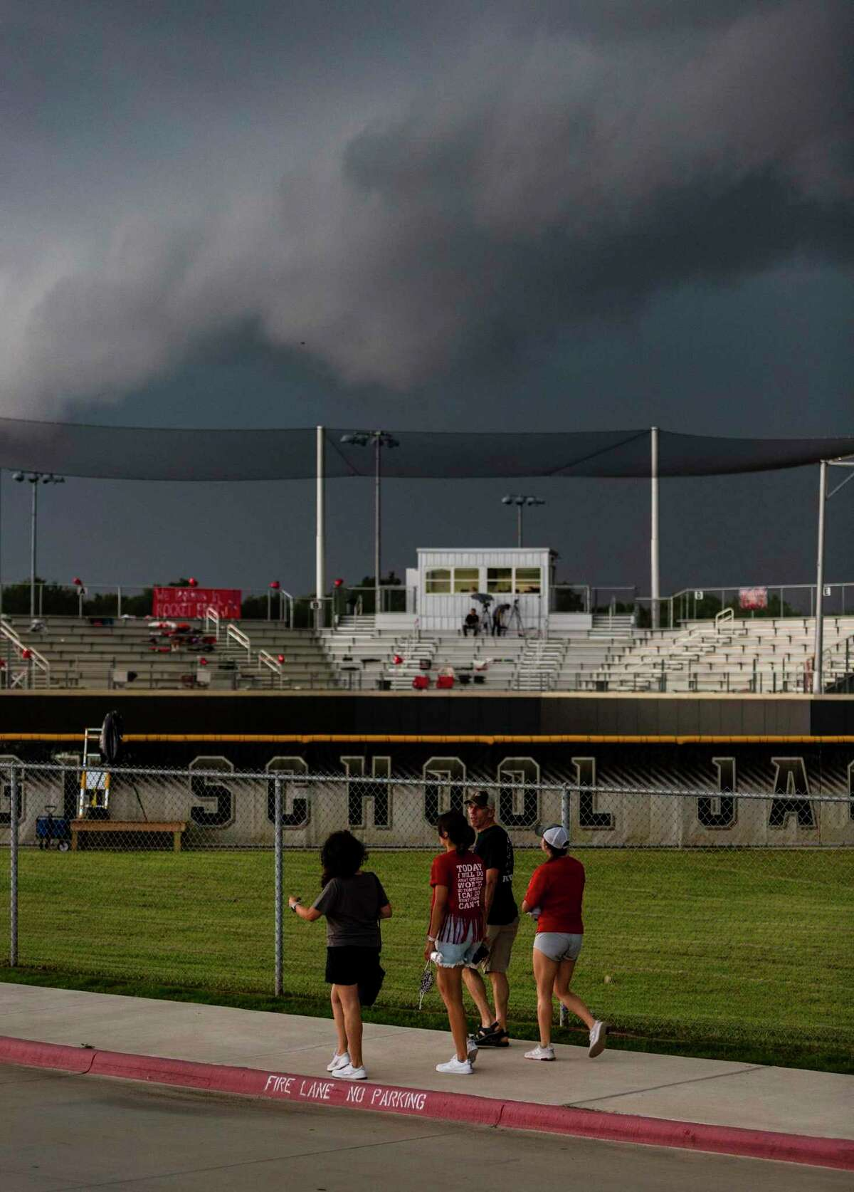 Fans leave the stadium Friday, May 28, 2021 at Johnson High School in Buda as storm clouds and lighting cause a game delay during Judson's Class 6A state quarterfinal softball game against Austin Bowie.