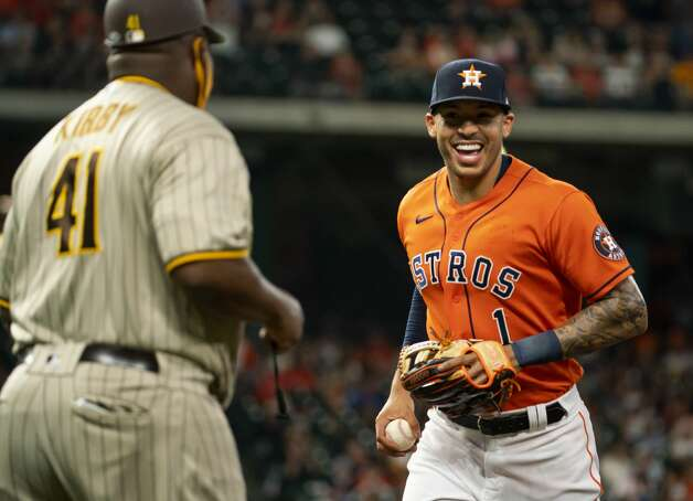 Houston Astros shortstop Carlos Correa (1) smiles at San Diego Padres first base coach Wayne Kirby (41) after nearly turning a double play during the first inning of an MLB game between the Houston Astros and San Diego Padres on Friday, May 28, 2021, at Minute Maid Park in Houston. Photo: Mark Mulligan/Staff Photographer / © 2021 Mark Mulligan / Houston Chronicle