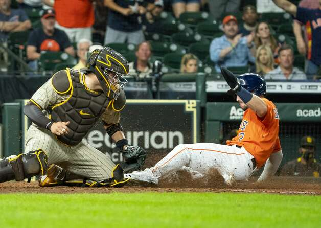 Houston Astros third baseman Alex Bregman (2) slides into home plate off of a sacrifice fly from Houston Astros right fielder Chas McCormick (20) to tie the score 3-3 during the tenth inning of an MLB game between the Houston Astros and San Diego Padres on Friday, May 28, 2021, at Minute Maid Park in Houston. Photo: Mark Mulligan/Staff Photographer / © 2021 Mark Mulligan / Houston Chronicle