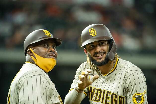 San Diego Padres shortstop Fernando Tatis Jr. (23) waves at a fan with San Diego Padres first base coach Wayne Kirby (41) after being intentionally walked during the tenth inning of an MLB game between the Houston Astros and San Diego Padres on Friday, May 28, 2021, at Minute Maid Park in Houston. Photo: Mark Mulligan/Staff Photographer / © 2021 Mark Mulligan / Houston Chronicle