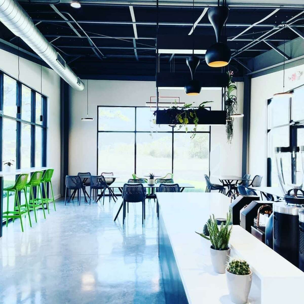 The interior features pendant lights hanging from the open ceiling revealing the maze of piping infrastructure that supports the café. The color palette sports a combination of pea green and gray chairs, with white quartz countertops, and light gray polished and sealed concrete floors.