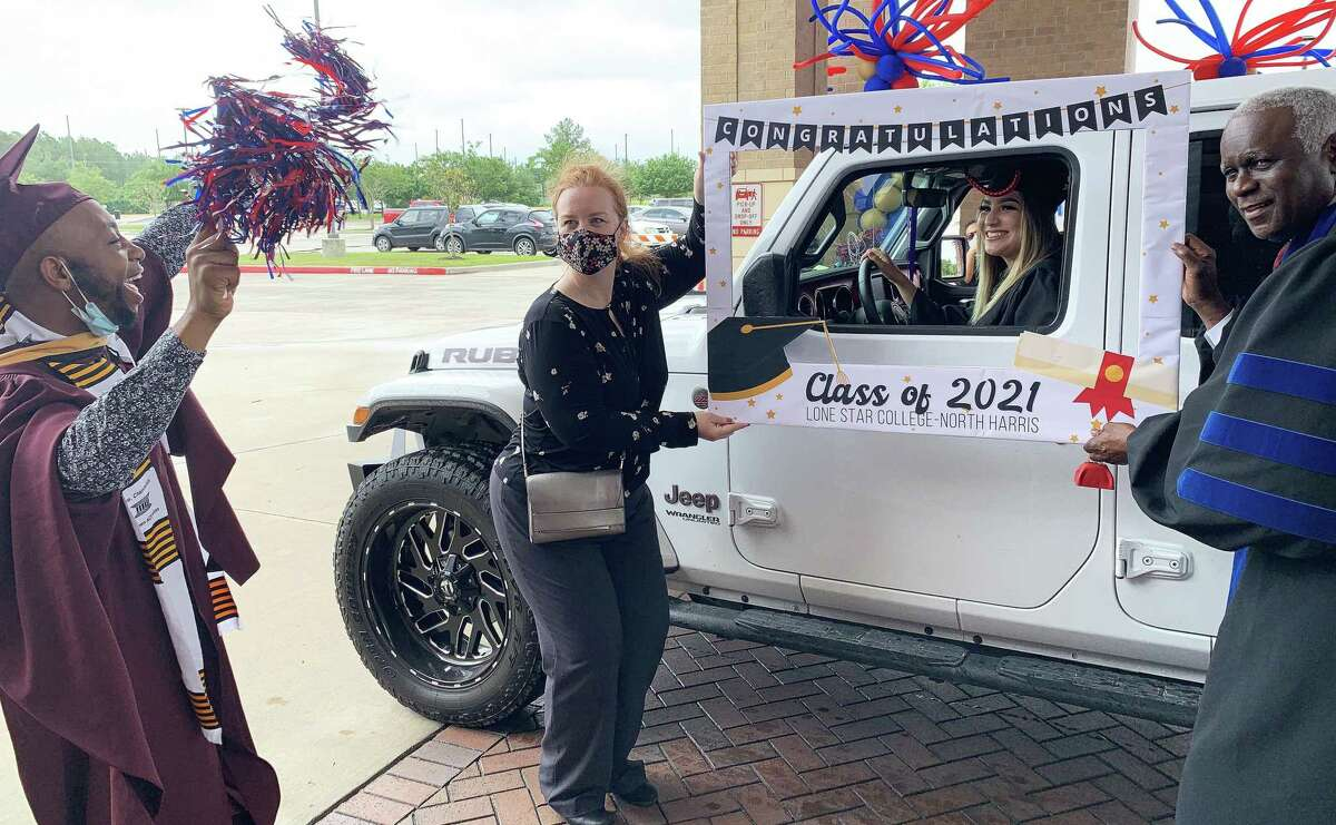 Students at Lone Star College-North Harris celebrated graduation with a drive-through party by stopping for a photo with a custom LSC photo frame. From left, Donald Chamberlain III from Student Outreach and Recruitment, Dr. Laura Yannuzzi, Vice President of Instruction, an LSC graduate, and Dr. Archie L. Blanson, president, LSC-North Harris.