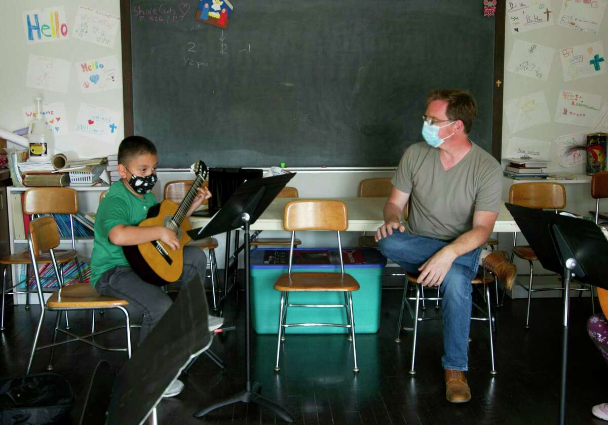 Teacher Scott Hill, with the music education nonprofit Intempo, watches student Jeremy Revolorio, 7, during one of its instrumental education sessions at Union Memorial Church in Stamford, Conn., on Thursday May 20, 2021. Intempo just received $100,000 from Fairfield County to further its New Arrivals initiative. The initiative is an instrumental and choral music education program that looks to address the arts, language, and social-emotional needs of children who are learning to speak English.