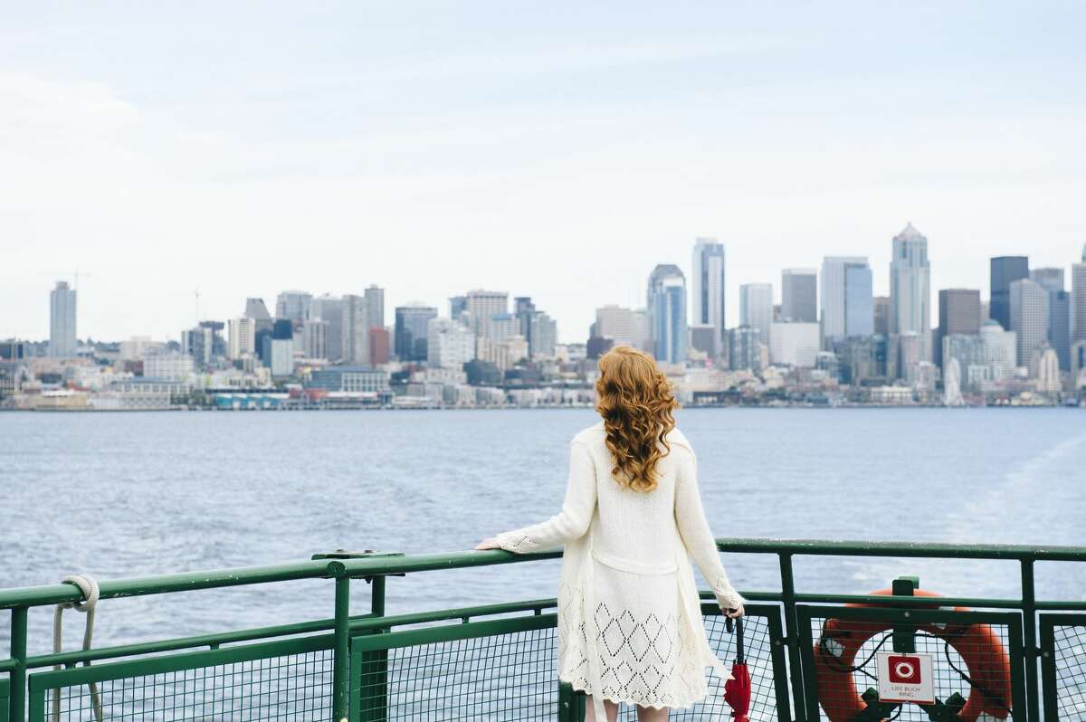 A woman standing on a ferry looking at the Seattle skyline.