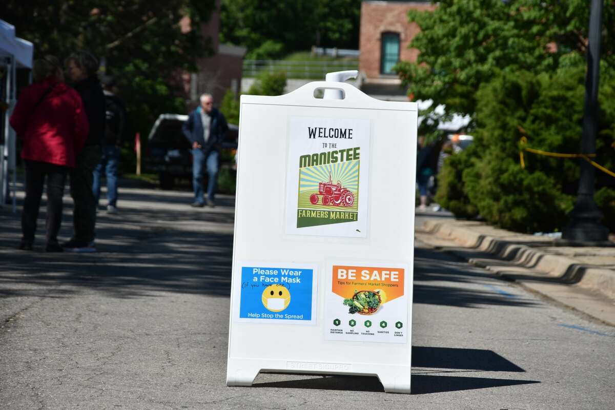 The Manistee Farmers Market features signs about wearing masks and other safety measures at the market.