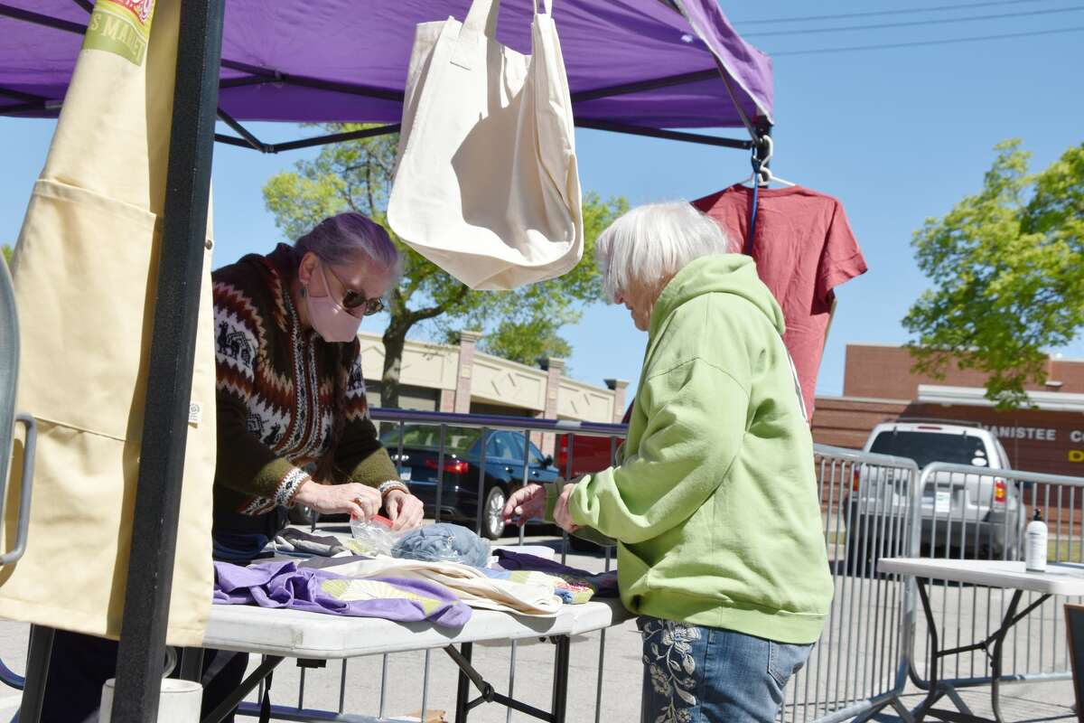 Market Manager Ramona DeGeorgio-Venegas helps a patron with a purchase of market merchandise for sale at the entrance area on Saturday, May 29.