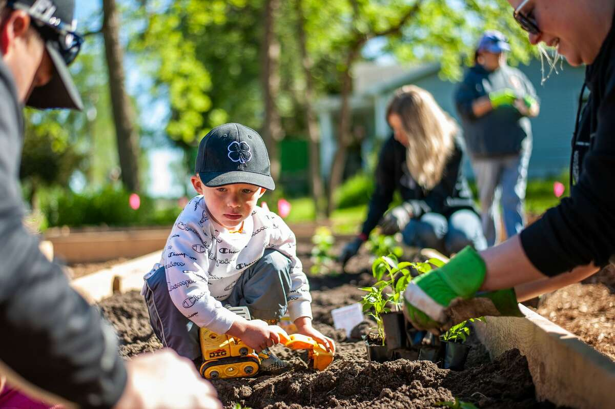 Sanford resident Blaine Swanton helps his parents dig holes in soil for the Sanford Grows community garden on May 29, 2021 near the Sanford Village Park.