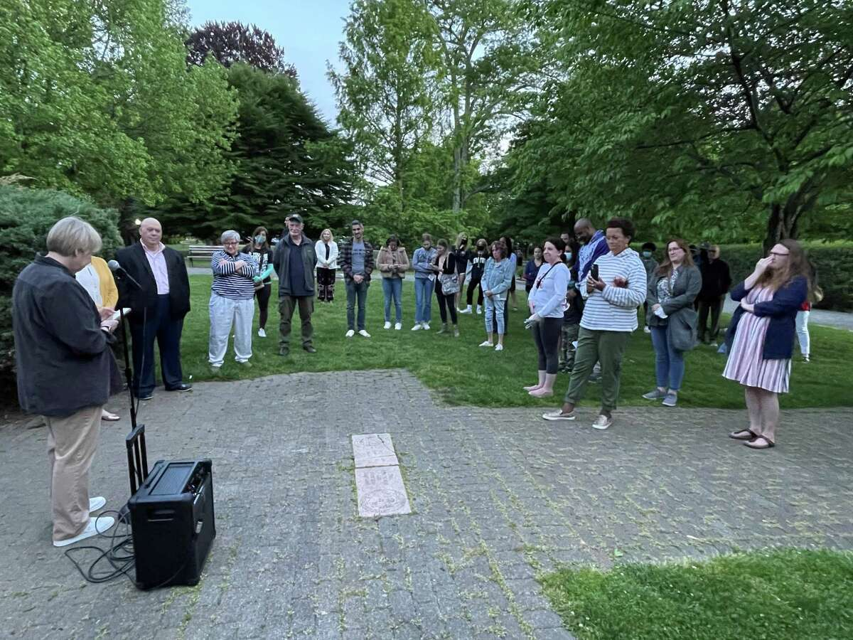 """Ridgefield Chorale's Artistic Director Daniela Sikora, left, leads vigil attendees in a rendition of """"Amazing Grace."""""""
