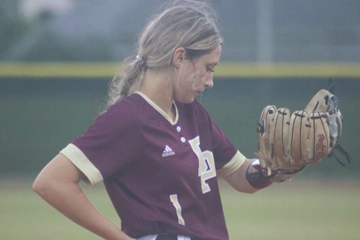 Third baseman Haidyn Hardcastle looks at her wristband for the next call during Friday night's game. Defensively, she caught two balls in foul territory.