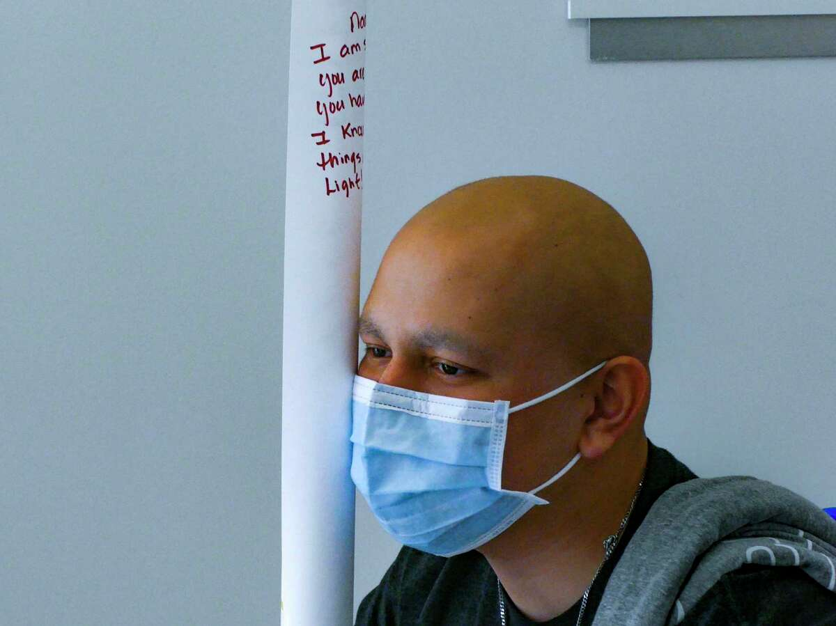 Noah Adams holds a rolled poster containing messages from staff at University Hospital on May 14. He rang a bell, a traditional signal that he is now cancer free.