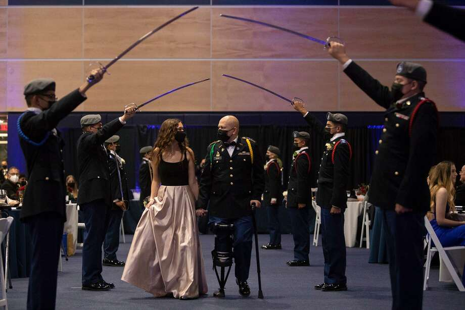Noah Adams walks with his girlfriend, Rachel Davis, through the saber guard at Central Catholic High School's Military Ball. Photo: Lisa Krantz /Staff Photographer / San Antonio Express-News