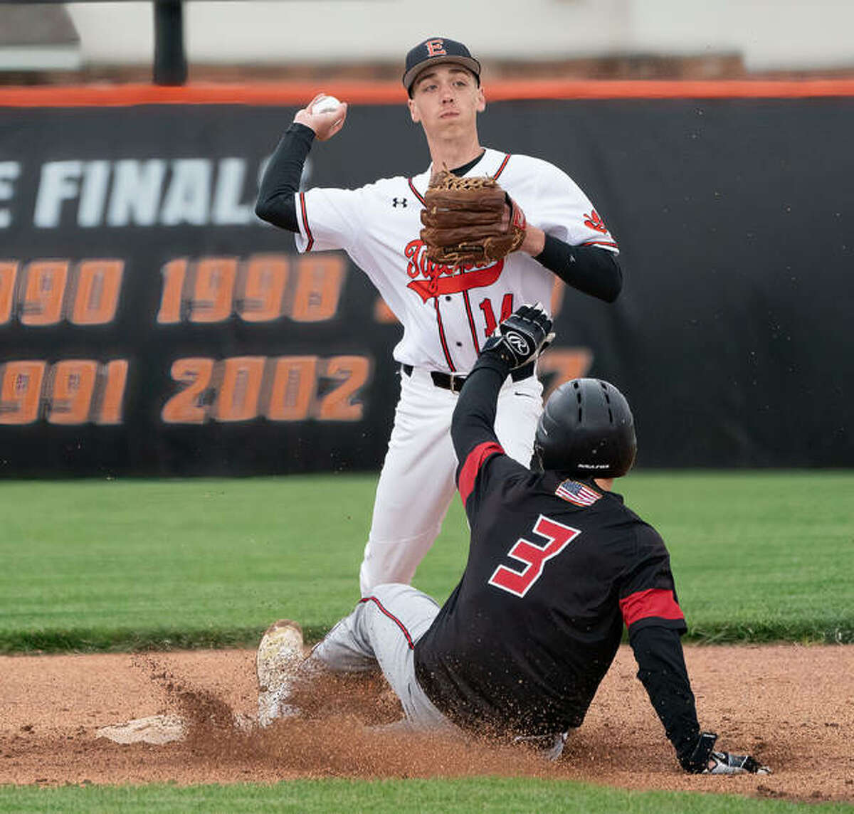 Edwardsville's Kyle Modrusic fires a throw to first base to try and complete a double play against Triad on Friday.
