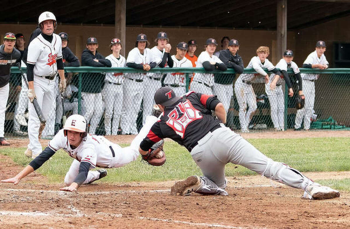 Edwardsville's Hayden Moore attempts to elude the tag of the Triad catcher as he slides across home plate in the first game of a doubleheader on Friday.