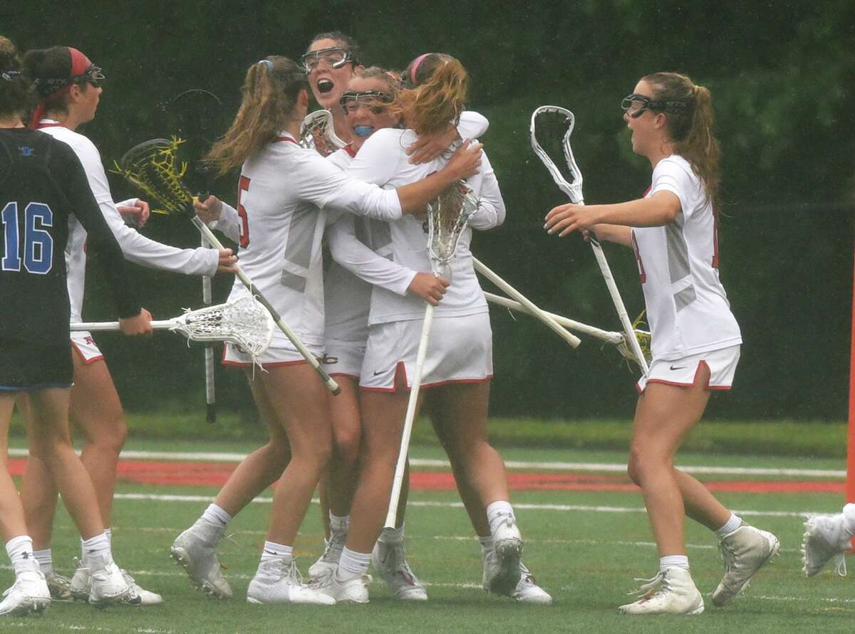 The New Canaan Rams celebrate a goal against Darien during the FCIAC girls lacrosse final at Dunning Field in New Canaan on Saturday.