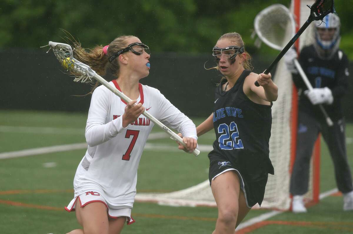 New Canaan's Devon Russell (7) carries the ball while Darien's Nelle Kniffin (22) defends during the FCIAC girls lacrosse final at Dunning Field on Saturday.