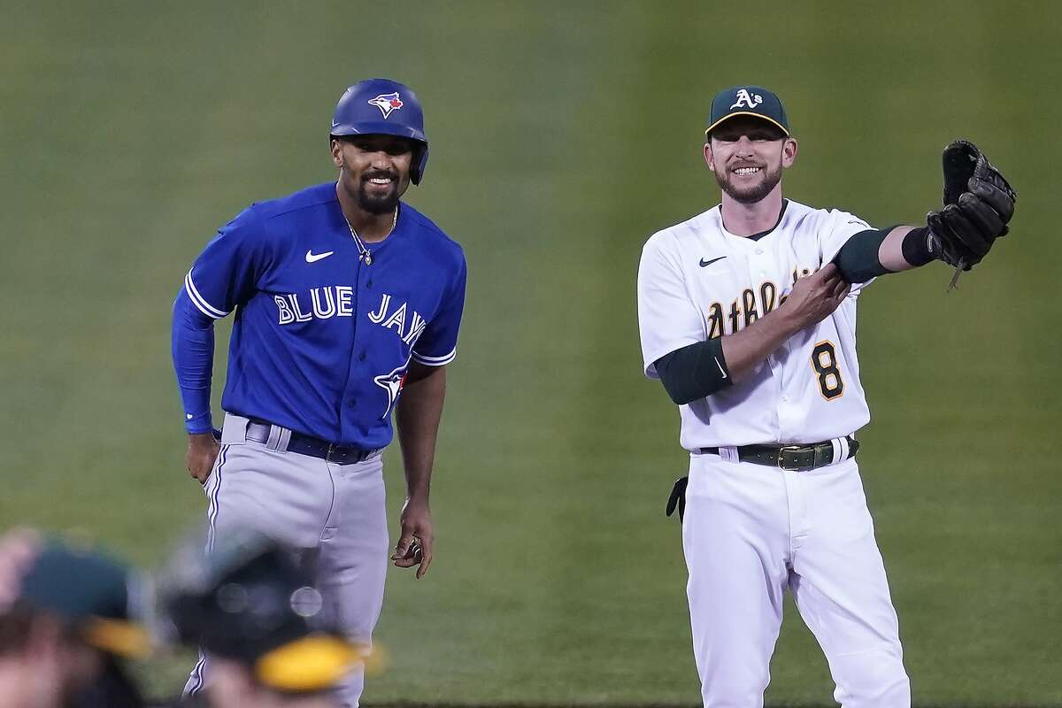 Toronto Blue Jays' Marcus Semien, left, talks with Oakland Athletics second baseman Jed Lowrie during a baseball game in Oakland, Calif., Tuesday, May 4, 2021. (AP Photo/Jeff Chiu)