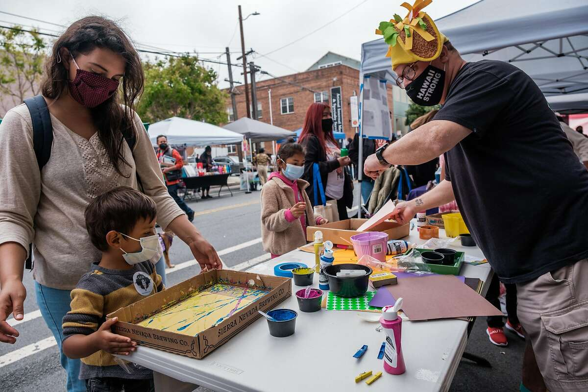 August Lopez of the Tenderloin Rec Center shows Liam Mota, 4, and his mother, Erika, his Magic Marble painting booth.