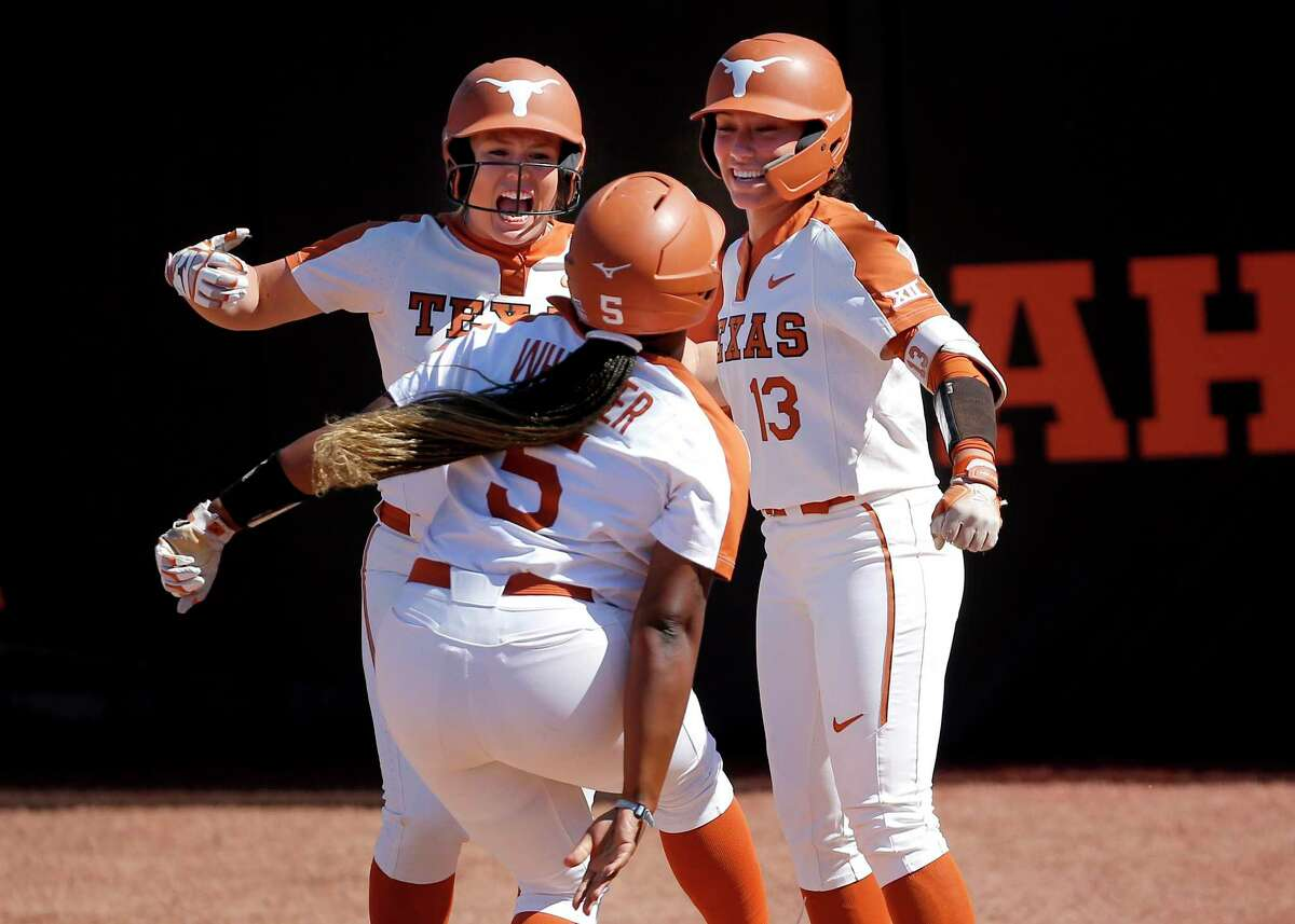 Taylor Ellsworth and Shannon Rhodes (13) celebrate a home run by Jordyn Whitaker, a freshman, in the sixth on Saturday. Whitaker's shot broke a 1-1 tie and preceded another Texas homer.