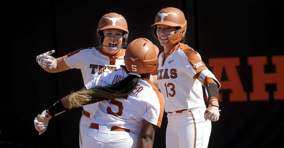 Texas' Taylor Ellsworth (17) and Shannon Rhodes (13) celebrate a home run by Jordyn Whitaker (5) in the sixth inning against Oklahoma State during an NCAA college softball super regional game in Stillwater, Okla., Saturday, May 29, 2021. (Sarah Phipps/The Oklahoman via AP)