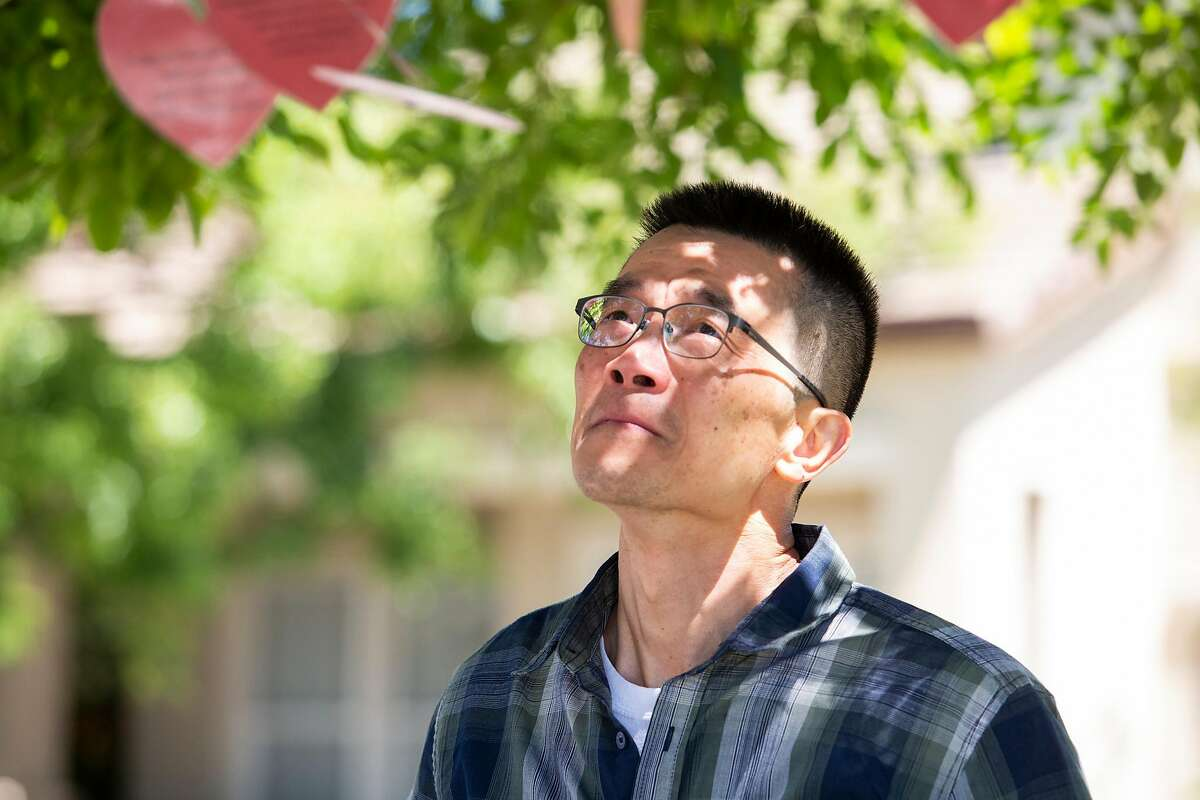 William Kuo, cries and reads a 'grievance heart' one of his neighbors strung in a tree for them outside their home in Dublin California on May 25, 2021.