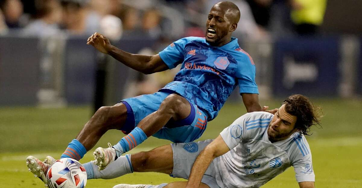 Houston Dynamo midfielder Fafa Picault, top, and Sporting Kansas City midfielder Graham Zusi (8) get tangled up while chasing the ball during the second half of an MLS soccer match Saturday, May 29, 2021, in Kansas City, Kan. Kansas City won 3-1. (AP Photo/Charlie Riedel)