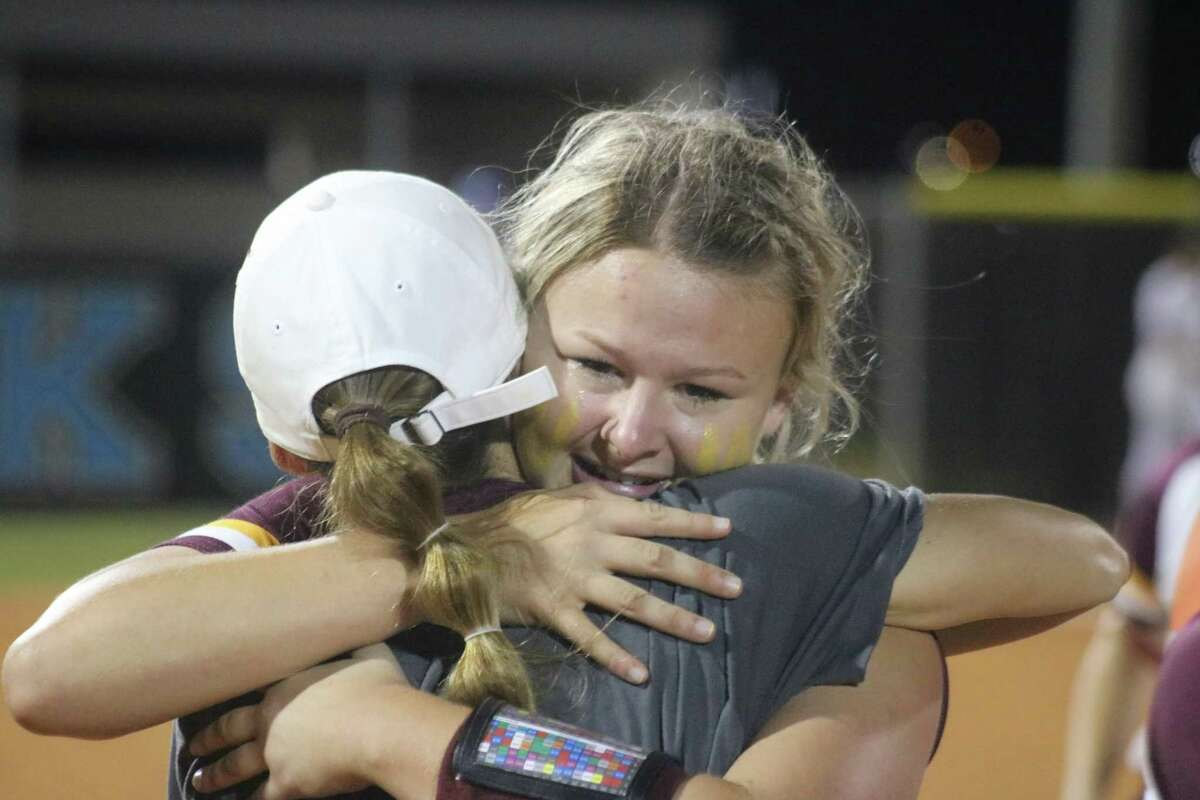 Haley Wilkerson gives assistant coach Danyell Hines a big hug during Deer Park's celebration Saturday night after winning the Region III title.