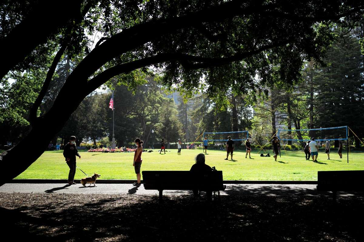 FILE - People enjoy the sunshine at a park in San Mateo on May 11, 2021.