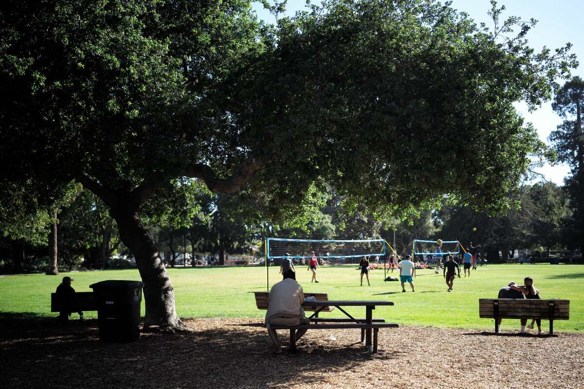 People enjoy the sunshine at a park in San Mateo.