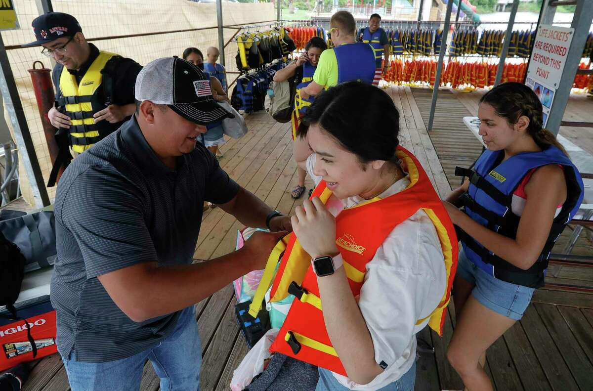 Josh Collazo, general manager of Nauti Dayz Boat Rental, helps Marlen Salinas properly secure a life vest, Friday, May 14, 2021, in Conroe. The business has invested more than $50,000 in changes, such as a new life jacket cage.