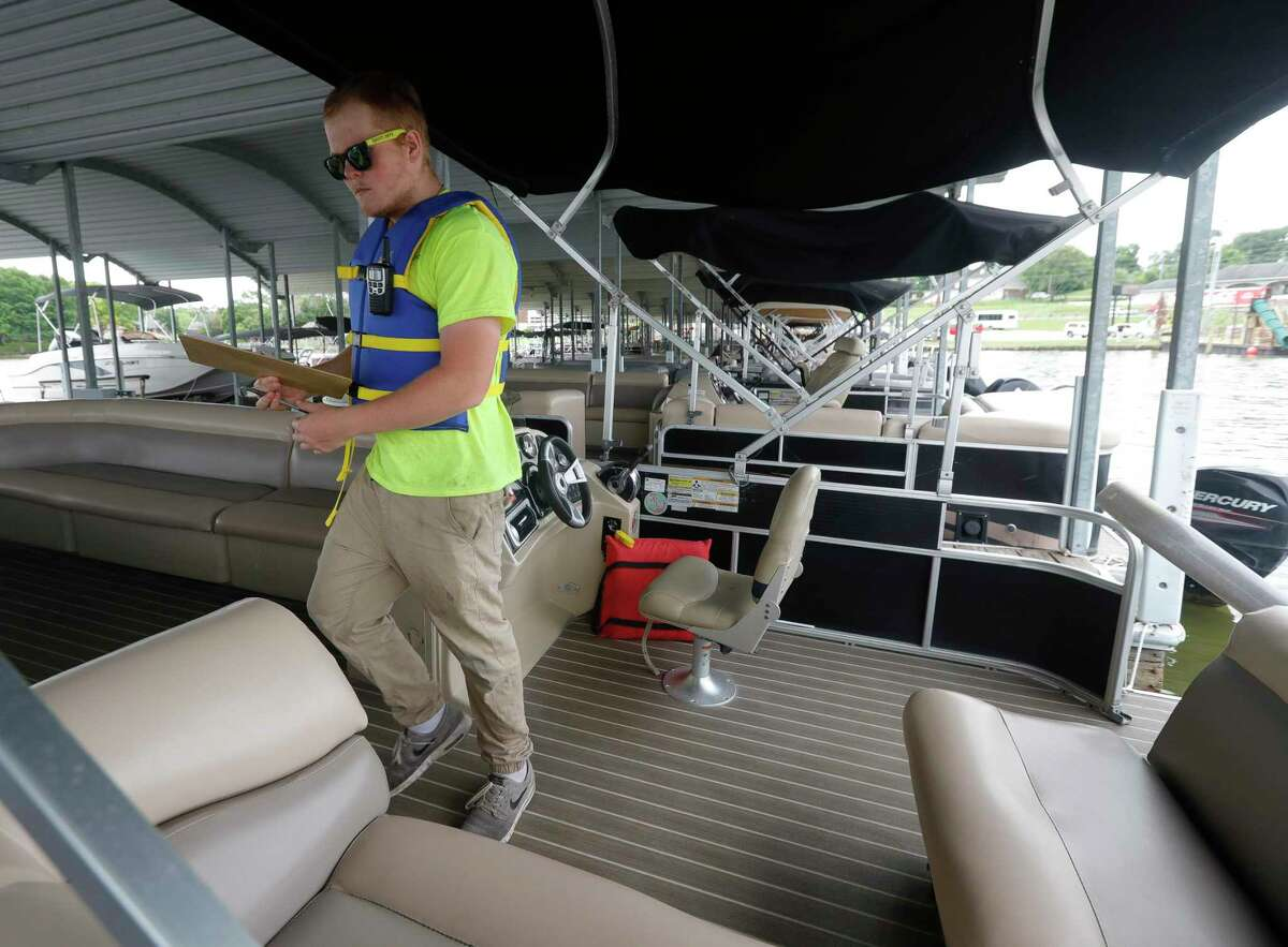 Christian Brownhill performs a safety check at Nauti Dayz Boat Rental, shows safety equipment available to renters, Friday, May 14, 2021, in Conroe. The business has invested more than $50,000 in changes, such as a new life jacket cage.