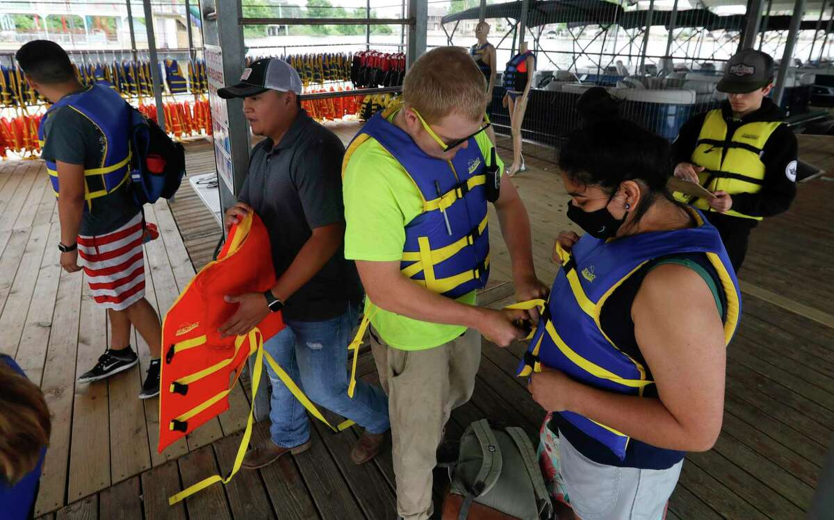 Christian Brownhill of Nauti Dayz Boat Rental helps properly secure life vests before boating on Lake Conroe.