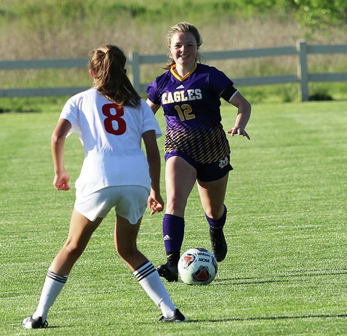 CM's Aubree Wallace (right) considers her options with the ball against Highland's Abby Huelsmann in a May 13 girls soccer match at the Bethalto Sports Complex. Wallace had three goals at home Saturday in a 5-4 loss to Breese Mater Dei.