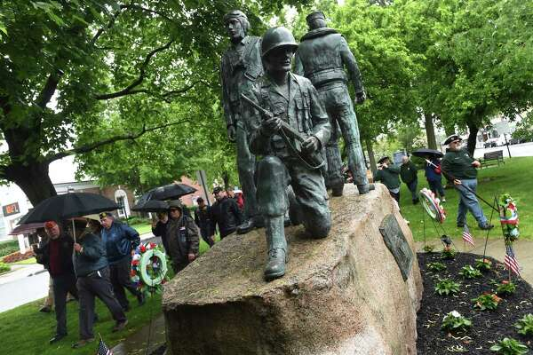 Veterans (left) and members of the Milford Volunteers Ancient Fife & Drum Corps (right) walk past the World War II monument during a Memorial Day wreath laying ceremony on the Milford Green on May 30, 2021.