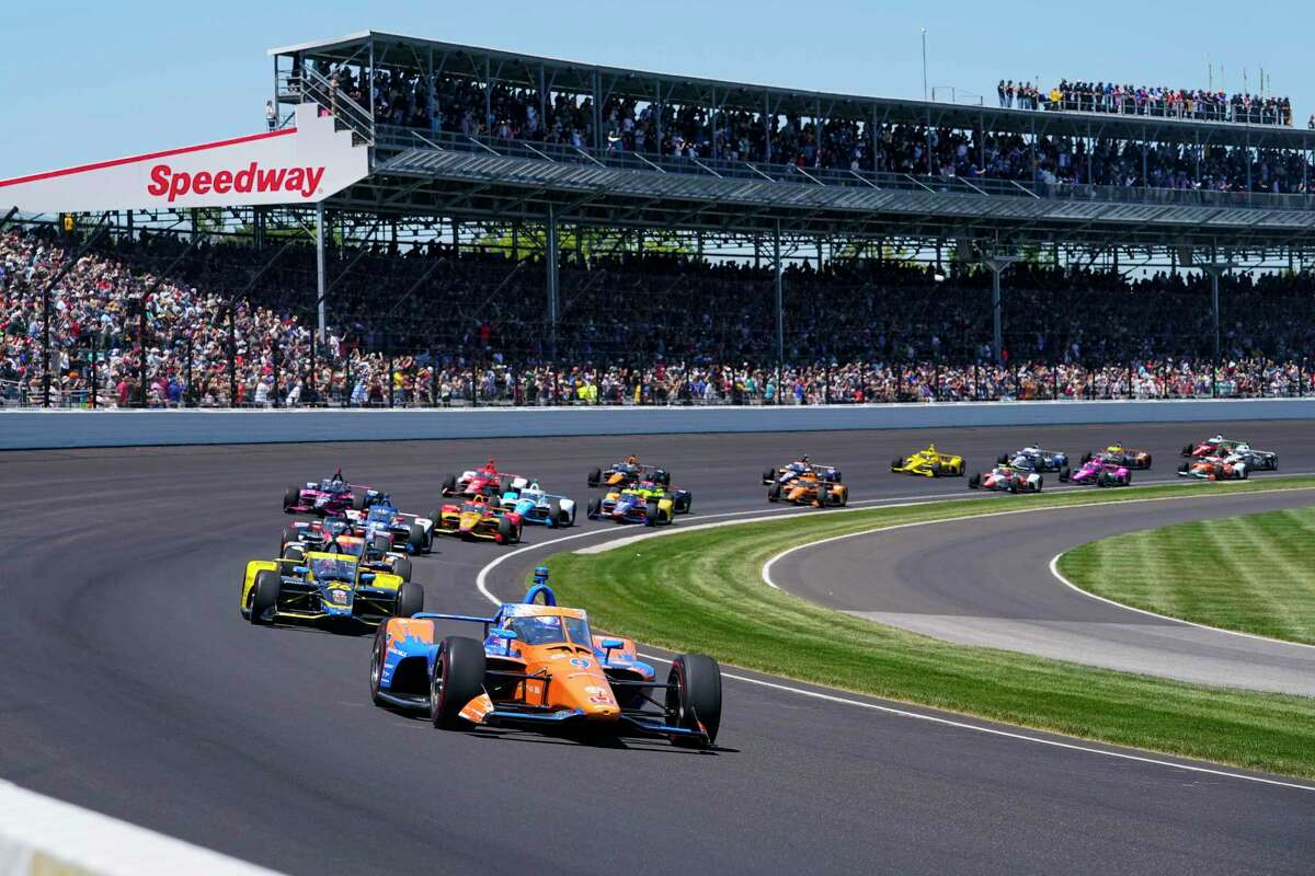 Scott Dixon of New Zealand leads the field through the first turn on the start of the Indianapolis 500 auto race at Indianapolis Motor Speedway in Indianapolis, Sunday, May 30, 2021.
