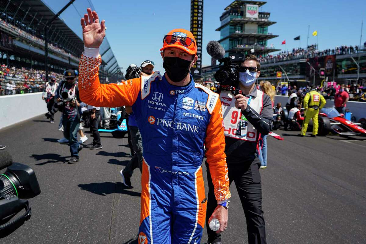 Scott Dixon, of New Zealand, waves to fans as he walks to his car before the Indianapolis 500 auto race at Indianapolis Motor Speedway in Indianapolis, Sunday, May 30, 2021.