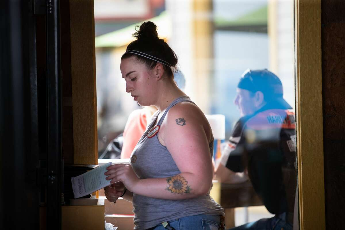 The Spot server Charlie Luke, 24, of Lake City works her server shift, Thursday, May 27, 2021, in Galveston Island. She started working recently at The Spot because of how busy the restaurant has been.