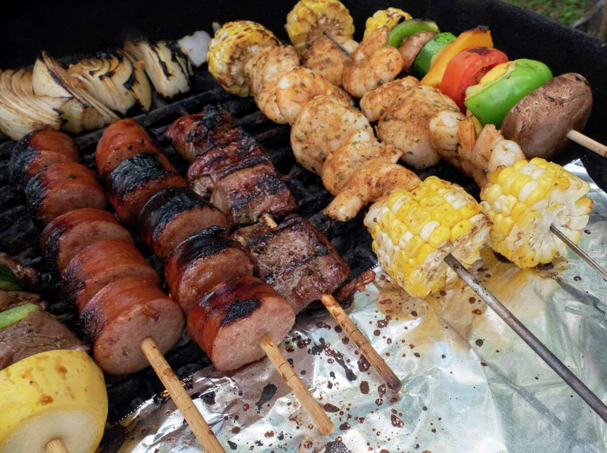 Kabobs are ready to be removed from the grill. The aluminum sheet keeps the end of the skewers from getting too hot to handle.